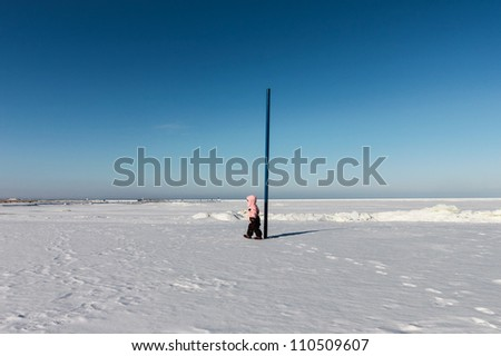 Child girl walks on snow near the sea