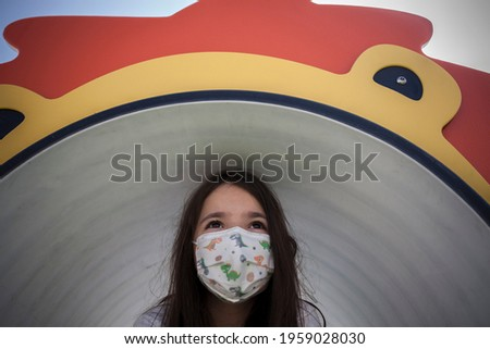 Child girl wearing face mask comming out of playground tunnel. Hopefull eyes for COVID-19 crisis concept Foto stock ©