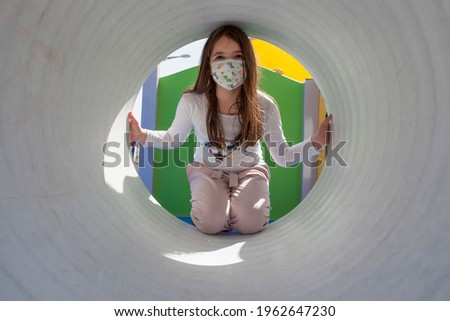 Child girl wearing face mask inside of playground tunnel. Hopefull eyes for COVID-19 crisis concept Foto stock ©