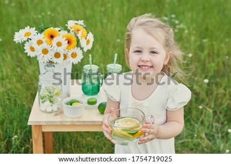 Child girl with lemonade. Lemonade and daisy flowers on table. Cozy morning. Spring and summer season card. Healthy Food and Drink. Summer holidays. Outdoor picnic. Mother's day card.