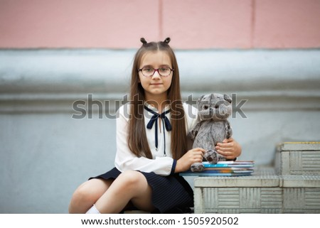 Child girl with plush toy and textbooks sits on the steps of the school stairs. Schoolgirl portrait. Selective focus.