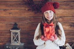 Child giving a Christmas present on rustic wooden background, farmhouse interior.