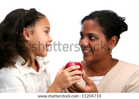 Child giving apple to her teacher