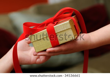 Child giving gift with red bow and golden box. Hand close-up.