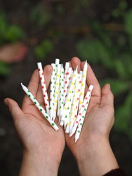 Child hads holding bunch of colorful Birthday candles. Celebration party object.Close-up.Polka dot candles. Happy Birthday concept, festive and holiday concept. Daylight,outdoor.