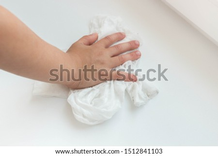 Child hand and white rag cleaning windowsill from dust.