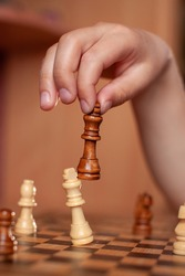 child hand holds chess piece of black king and knocks down opponent's piece- white king.