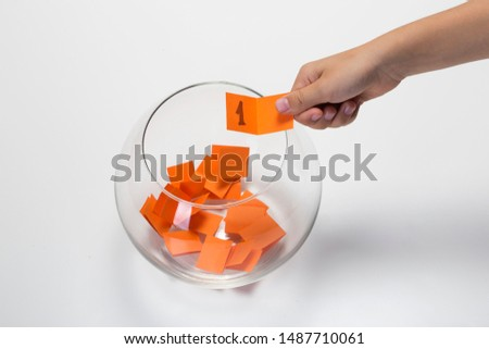 Child hand picking ticket with number one from a glass bowl, random name ballot, simple raffle Foto d'archivio ©