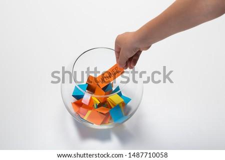 Child hand picking winner from a glass bowl, random name ballot, simple raffle Foto d'archivio ©
