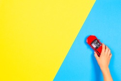 Child hand playing red toy car on light blue and yellow background