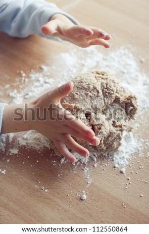 Child hand preparing dough for Christmas cookies