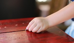 Child hand put a coin in donation box