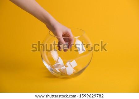 Child hand randomly picking a paper from a glass bowl, random name ballot, simple raffle Foto d'archivio ©