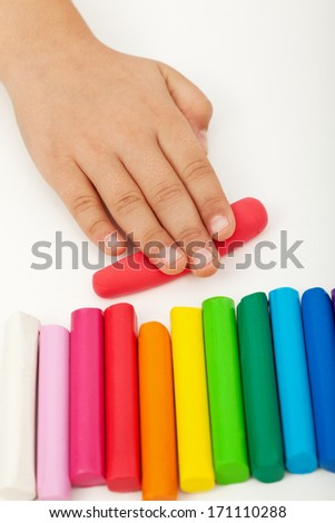 Child hand with colorful modeling clay bars