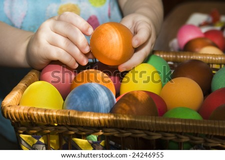 Child hands holding a multi colored egg.