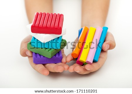 Child hands holding colorful modeling clay bars and blocks