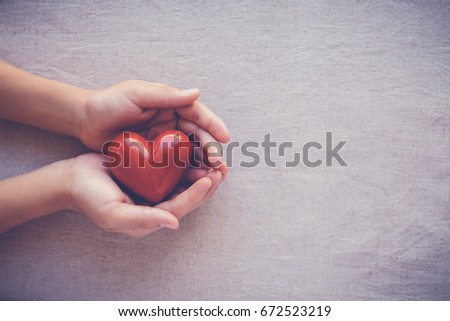 child hands holding red heart, health care, love and family concept, world heart day #672523219