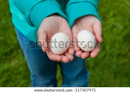Child hands holding two eggs. This image shows the two hands of a child holding two fresh eggs.