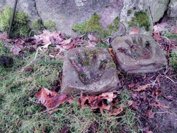 Child hands imprinted in two stones which are layered on the ground with leaves and grass
