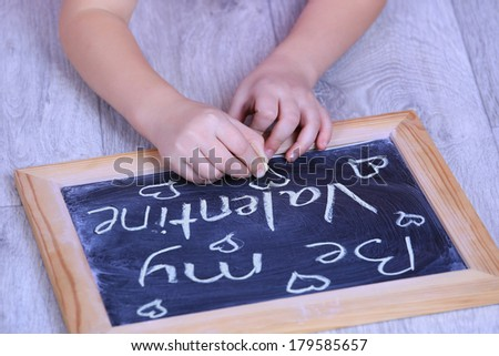 Child hands on a paper size chalkboard saying Be my valentine no face