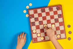 Child hands playing checkers on checker board game over yellow and blue background, top view