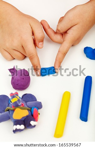 Child hands playing with colorful clay - closeup