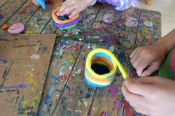 Child hands playing with colorful clay. Colorful dough on table in school. Plasticine for children, funny fish from modeling clay in kindergarten.