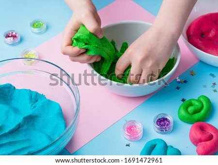 Child hands playing with colorful clay. Homemade plastiline. Plasticine. play dough. Girl molding modeling clay. Homemade clay.