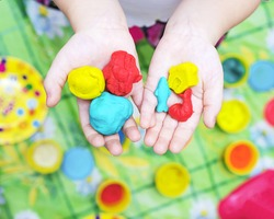 Child hands playing with colorful clay, plasticine in children's room, Creative playing with baby play dough, hands holding hand-made plasticine toy, making plasticine figures