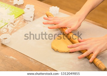 Child hands preparing Christmas cookies dough with wooden rolling pin in cozy kitchen for the winter holidays. Copy space.