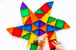 Child hands putting together a star pattern with magnet tiles.  Construction play concept.