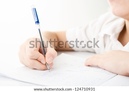 Child hands writing a homework by closeup