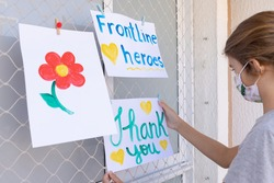 Child hanging positive messages to frontline heroes working during Coronavirus (COVID-19) quarantine. Thank you message.