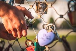 Child hangs padlock on the bridge. Heart shaped padlock.