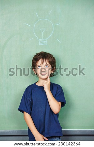 Child has an idea with lightbulb over his head drawn on a chalkboard in school