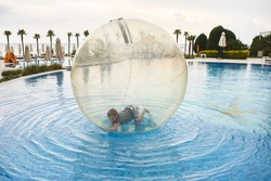 Child have fun inside big plastic balloon on the water of swimming pool on the summer resort. Little boy inside big inflatable transparent ball running and having fun.