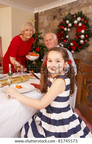 Child having Christmas dinner with grandparents