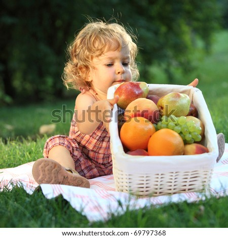 Child having picnic in summer park. Shallow depth of field