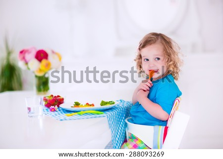 Child having vegetables for lunch. Healthy fruit and vegetable meal for children. Kids eat in a white dining room or kitchen. Toddler kid having breakfast. Food for preschooler at home or daycare.