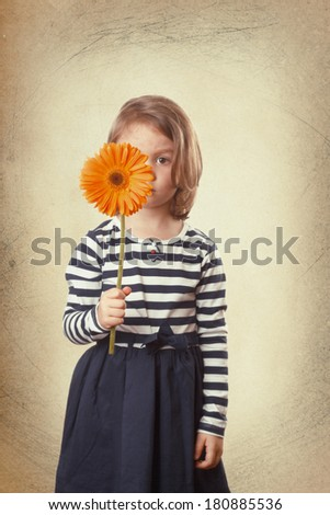 Child hiding his face behind a orange gerbera flower