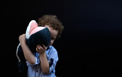 child hiding his face behind a stuffed animal