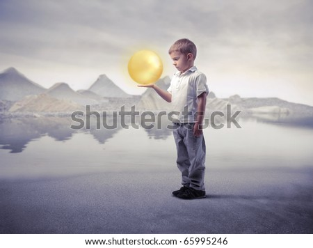 Child holding a bright sphere with lake on the background