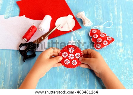 Child holding a Christmas ball in his hands. Child shows Christmas ball. Christmas tree crafts, scissors, thread, needles, felt scraps on a blue background. Sewing concept