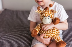 Child  holding a giraffe plush toy on a gray background