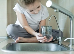 Child holding a glass under stream of clear transparent cold water from a tap. Close up shot of a young girl pouring a glass of fresh water from a kitchen faucet. Healthy Nutrition. World Water Day.