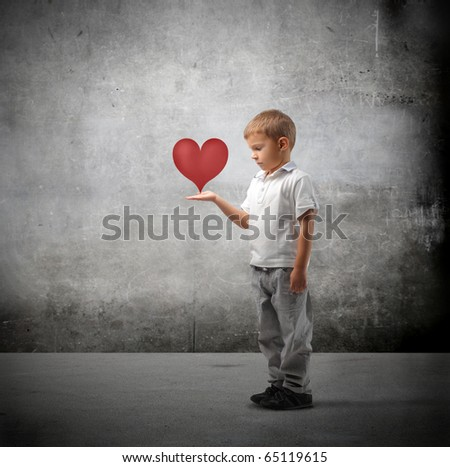Child holding a heart in his hands - stock photo