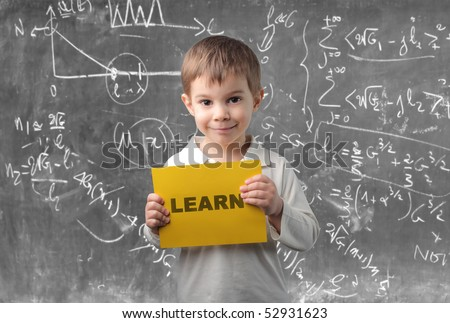 Child holding a sheet with learn written on it