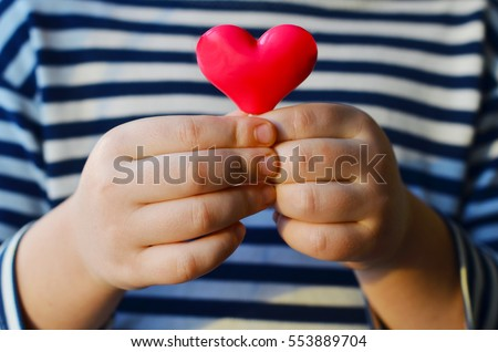 Stock Photo child holding a small pink heart. symbol of love, family, hope. Backgrounds for cards on Valentine's Day. Backgrounds for social posters about the preservation of the family and children.