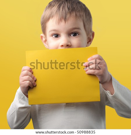 Child holding a yellow paper sheet