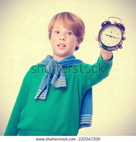 Child holding an alarm clock and concerned about the time